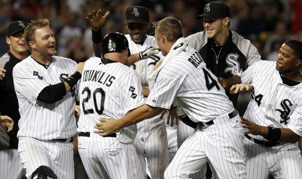 White Sox players mob Youkilis after he hit game-winning single in MLB baseball game against Rangers in Chicago